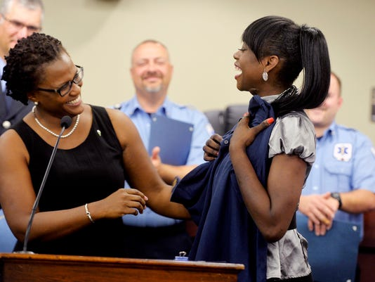 York Mayor Kim Bracey presents Dinnell Clarke, 25, with a York City Fire Department polo shirt at the York City Fire Department Awards Ceremony on Thursday, Aug. 28, 2014, at York City Hall. A burn victim thanked a dozen of her emergency responders, a fire captain was promoted and four retiring firefighters and 2013 Firefighter of the Year were recognized during the ceremony.