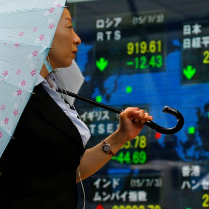 A woman looks at an electronic stock indicator of a