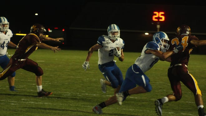 Drake Brezina (2) is expected to be one of eastern Iowa's top running backs this fall. The Clear Creek Amana senior, here finding the hole in the Mount Pleasant defense, rushed for 206 yards and two touchdowns in the Clippers' 23-8 win Friday in Mount Pleasant. This run came on the first of his two scoring plays.