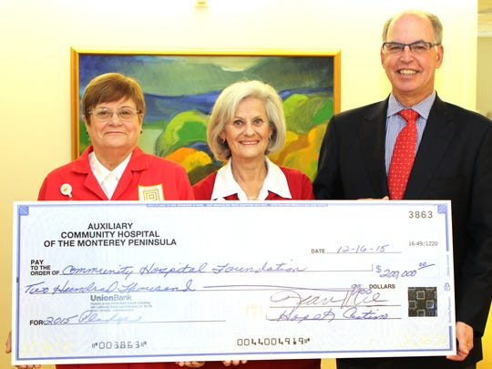 Steven Packer, MD, president/CEO of Community Hospital, receives a $200,000 gift from Hope Cutino, left, Auxiliary treasurer, and Jean Kane, Auxiliary president.