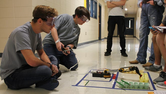 Jacob Smith watches as Austin Beck maneuvers a robot to place a Lego block into an egg carton during competition at the Mississippi Gulf South Regional Science Olympiad at Pearl River Community College. The team from Forrest County Agricultural High School placed first in the event.
