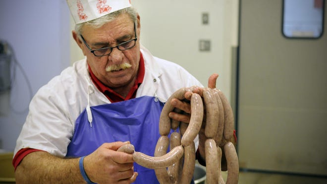 Steve Sellnow of the St. Joseph Meat Market prepares to put fresh sausage onto a rack to be smoked. The butcher shop won three awards at the 2015 American Cured Meat Championships.