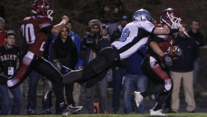 Lansing Catholic's Eli Whitney stops Portland's Cole McGregor during a game last fall. The unbeaten Cougars and Raiders meet Friday in a key CAAC White contest. Lansing Catholic and Portland split its two meetings last fall.