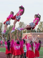 Canton cheerleaders, all wearing pink shirts, perform