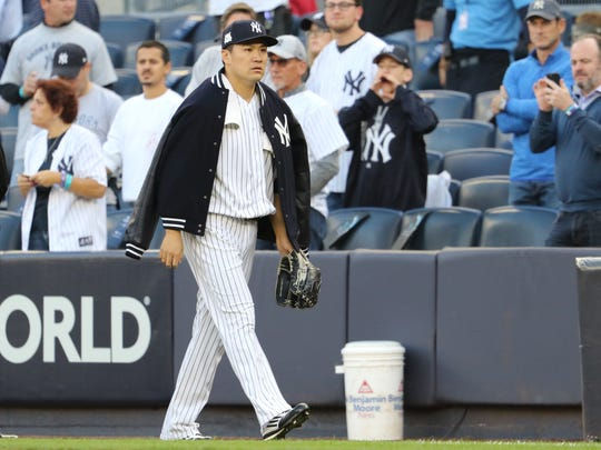 Masahiro Tanaka heads to the dugout just before the first pitch, Wednesday, October 18, 2017.