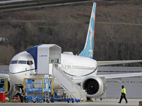 A worker walks next to a Boeing 737 MAX 8 airplane