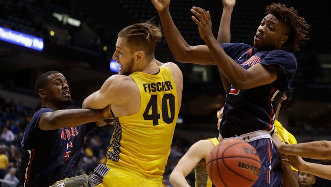 Marquette's Luke Fischer battles for a rebound with Howard's Marcel Boyd (left) and Damon Collins. Fisher injured his shoulder on Monday night, but not seriously.