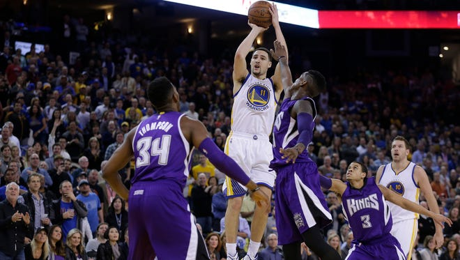 Klay Thompson shoots over the Kings' defense in the third quarter Friday night.