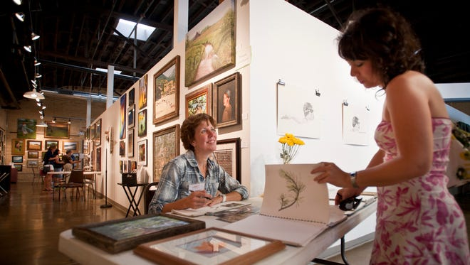 Chanda Davetas pages through some sketch books created by Amy Jo Eliason at the ARTgarage  during Gallery Nite.