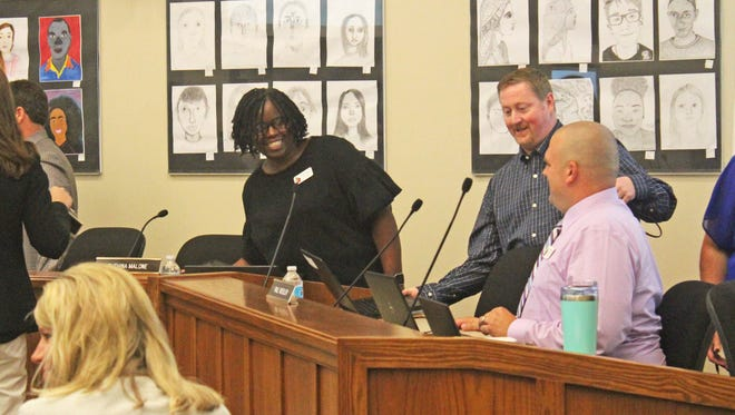 New Iowa City Community School Board members Ruthina Malone (left) and Shawn Eyestone (center) take their seats at the board table beside board member Paul Roesler on Sept. 26, 2017.
