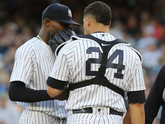 Yankee starting pitcher Domingo German, left, talks