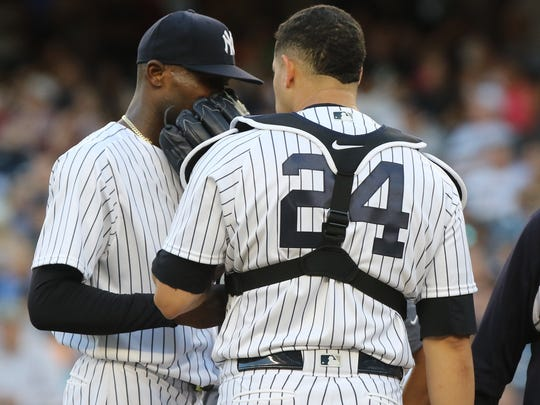Yankee starting pitcher Domingo German, left, talks with catcher Gary Sanchez as German struggled in the first inning against the Mets on Friday, July 20, 2018.