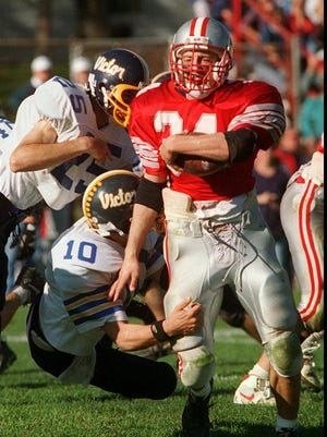 Canandaigua's Billy Greene breaks past Victor's Erich Camping, #25, for a first-half gain, October 15, 1994.