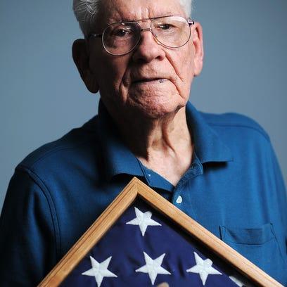 Ken Salisbury, 92, holds an American flag that he has