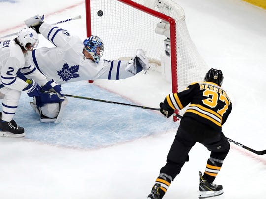 Boston Bruins center Patrice Bergeron (37) beats Toronto Maple Leafs goaltender Frederik Andersen for a goal during the first period of an Game 1 of an NHL hockey first-round playoff series Thursday, April 11, 2019, in Boston. At left is Maple Leafs defenseman Ron Hainsey. (AP Photo/Charles Krupa)