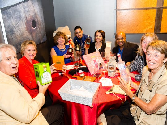 Robert and Karen DiBenedetto, from left, Kimberly Delcomyn-Javarinis, Wilfredo Ramos, Kate Rypina, Jean Marie Saintyl, Amy Cooper and Carolyn Kasischke show off prizes won from live auctions.