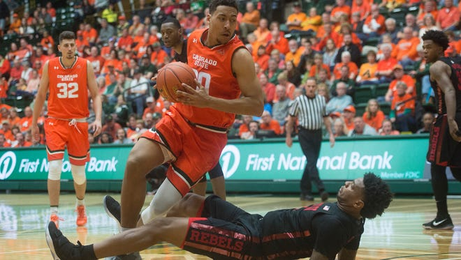 UNLV forward Tervell Beck falls to the court as CSU Deion James drives the ball to the basket during a game at Moby Arena on Saturday, January 20, 2018 in Fort Collins, Colorado. The play resulted in a charging call against the Rams.