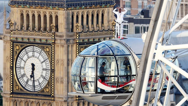 British athlete Mo Farah stands atop of a pod on the London Eye, with Big Ben's clock tower in background, as he bids a final farewell to British track competitive athletics.