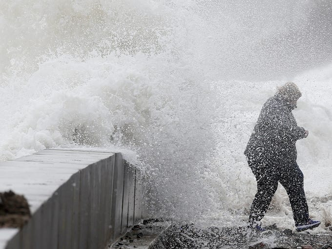 A woman gets caught by a wave as heavy seas continue