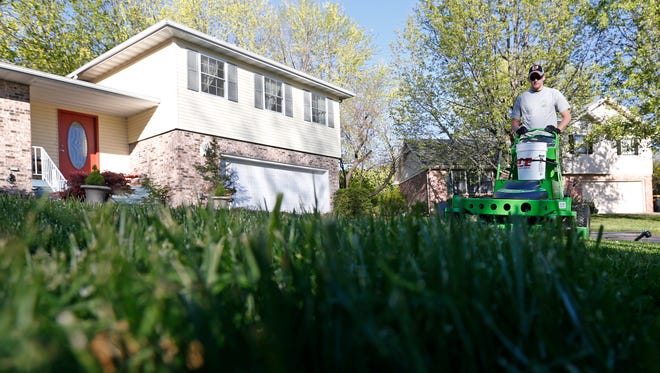 Mike England, an employee of Green Tech Lawn Care, mows a lawn in south Springfield with a solar powered electric mower.