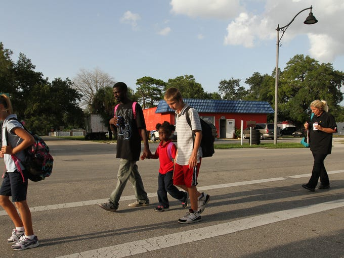 Alyssa, 10, leads the family to the Salvation Army in Fort Myers after having dinner from Sally's Cafe next door. Lannie, his 5-year-old daughter Cassy, 13-year-old Austin and his mother Shanda, follow.