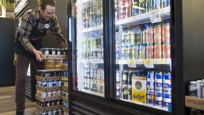 Trent Chavez, an employee of Pringle's on West Drake Road, replenishes the liquor store's stock of beer Wednesday, January 27, 2016. Your Choice Colorado aims to bring the idea of full-strength wine and beer to grocery stores around the state.
