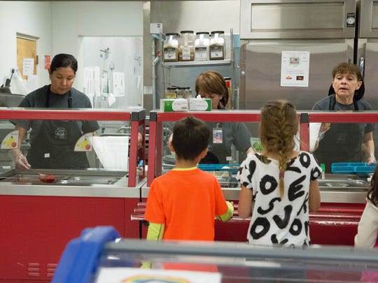 Raquel Carrasco,left, Lisa Palacios,center and Carment Reyes,right, serve lunch to first and second graders at Alameda Elementary School, Tuesday February 28, 2017. Las Cruces Public Schools announced they would be launching a new mobile application and webpage that gives parents a view of the lunch menus and nutritional information of the lunches.