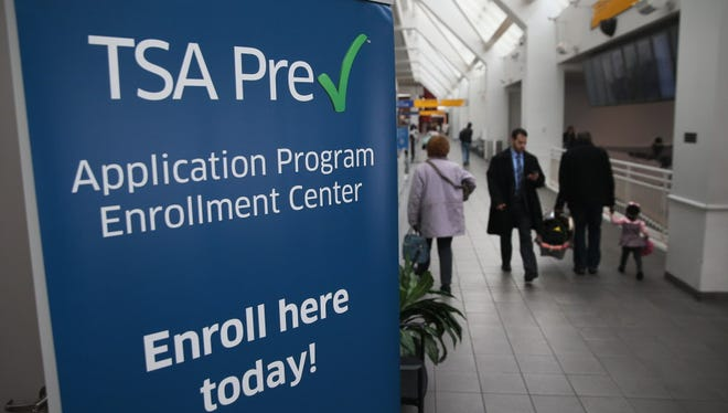 Travelers walk past a TSA Pre-check application center at Terminal C of the LaGuardia Airport on January 27, 2014.
