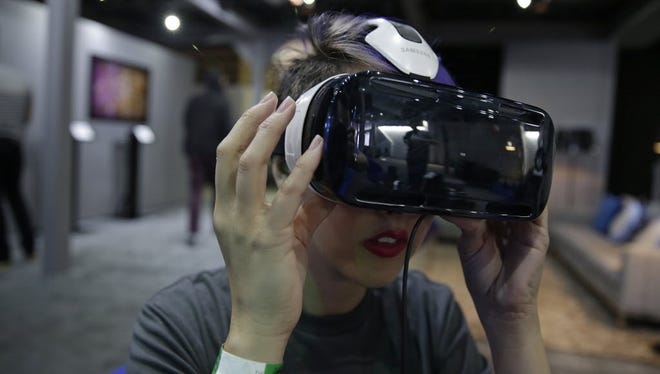 A woman demonstrates the Oculus virtual reality headset at the Facebook F8 Developers Conference on March 26, 2015, in San Francisco.