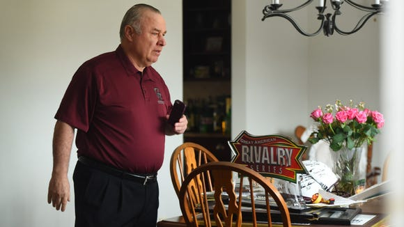 Don Bosco former coach Greg Toal stands in front of all his memorabilia and other things on the table brought to him by a group of current Don Bosco Prep football players to his home on Sunday morning as a show of support for their coach, who they feel was wrongly forced to resign by school officials.