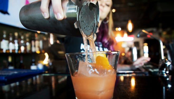 Graylyn Lechance, a bartender at Nevermind Awesome Bar and Eatery pours an old fashion for a photograph.