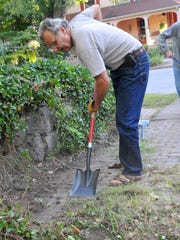 Cecil Bothwell works to clear the sidwalk on Blake Street in Montford in 2010. He led volunteers on the weekends in cleaning up old sidewalks that had become covered by vegetation or otherwise impassible.