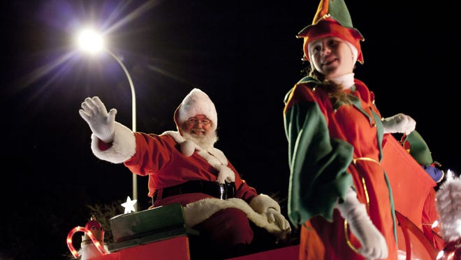 Santa and his elves wave from a sleigh during the 2014 Santa Parade in St. Clair.