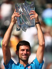Novak Djokovic of Serbia hoists the trophy after winning his third straight and fifth total BNP Paribas Open title Sunday, March 20, 2016, in Indian Wells, Calif., following the men's final against Milos Raonic of Canada. Djokovic won in straight sets, 6-2, 6-0.