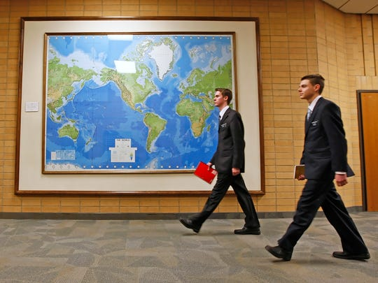 In this Jan. 31, 2008, file photo, two Mormon missionaries walk past a large map of the world in a hallway at the Missionary Training Center in Provo, Utah. Mormon missionaries will remain in Russia despite the country's new anti-terrorism law, which will put greater restrictions on religious work starting later this month. In a statement issued Friday, July 8, 2016, the Church of Jesus Christ of Latter-day Saints said that missionaries will respect a measure that Russian President Vladimir Putin signed into law this week.
