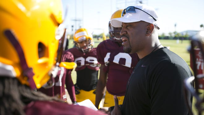 ASU assistant coach DelVaughn Alexander talks to his wide receivers during Spring practice at the Kajikawa practice fields at ASU  in Tempe in 2014.