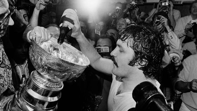 Flyers goalie Bernie Parent celebrates by pouring champagne into the Stanley Cup in 1974.