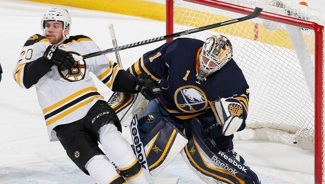 Daniel Paille #20 of the Boston Bruins falls in front of Jhonas Enroth #1 of the Buffalo Sabres at First Niagara Center on February 26, 2014 in Buffalo, New York.