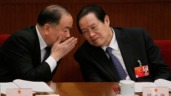 Zhou Yongkang, right, then Chinese Communist Party Politburo Standing Committee member in charge of security, listens to Wang Lequan, deputy chairman of the party's Political and Legislative Affairs Committee, during a plenary session of the National People's Congress at the Great Hall of the People in Beijing in March 2012.