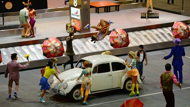Artists from 'The Beatles LOVE by Cirque du Soleil' perform in the baggage carousel area at McCarran International Airport in celebration of the 50th anniversary of The Beatles' only Las Vegas appearance.