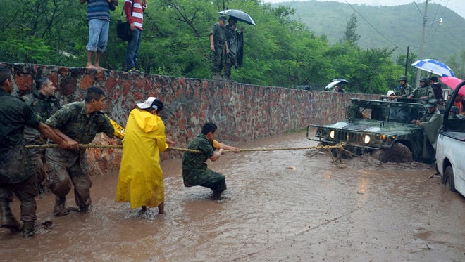 Army soldiers work to try to get their vehicle out of a flooded portion of a road caused by Tropical Storm Manuel in the city of Chilpancingo, Mexico on Sunday.