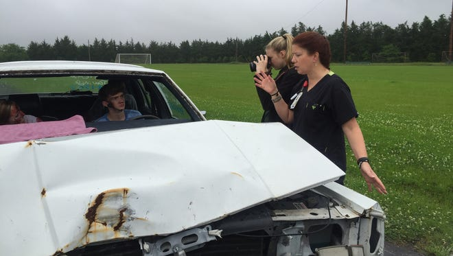 Theresa Hood (right), a nurse and the director of education at Rapides Regional Trauma Center, gives instructions to Jeremiah Newton (left) before the mock crash on Friday morning at Rapides High School.