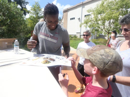 FSU Senior Center Kai James signs an autograph for Tristan Shivers, 10, and his grandmother Rita Shivers during the FSU Women's Block Party at Miracle plaza on Saturday where fans got the opportunity to meet their favorite players.