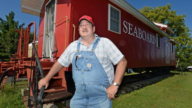 Jerry Bruce stands by a train caboose in his yard. Bruce, who says the American Pickers television show owes him $1,000 and he has a court judgment to prove it, plans to collect when the show comes back to the Upstate.
