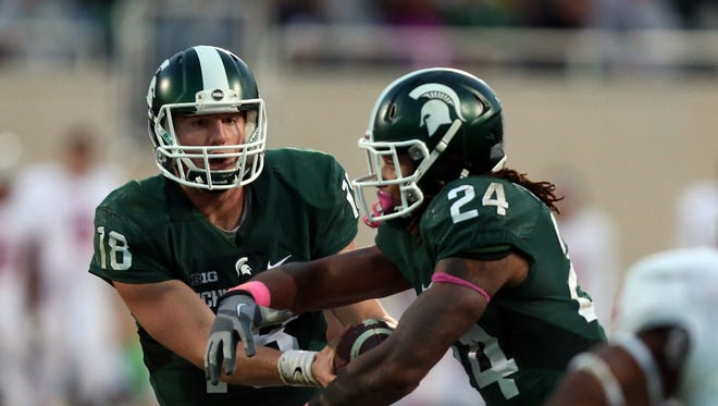 Michigan State quarterback Connor Cook hands off to running back Gerald Holmes (24) during second-half action on Saturday, Oct. 24, 2015, at Spartan Stadium in East Lansing, Mich.