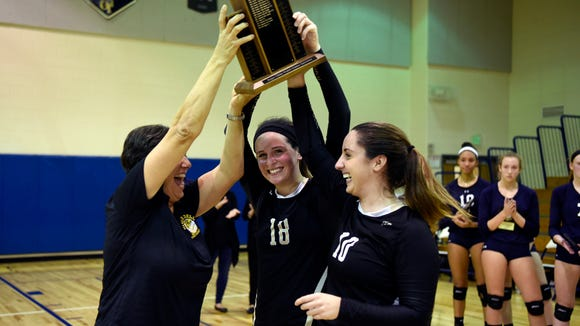 River Dell head coach Dianne Furusawa holds up the 2016 Bergen County volleyball championship trophy with Meredith Currlin (18) and Christa Passaretti (10).
