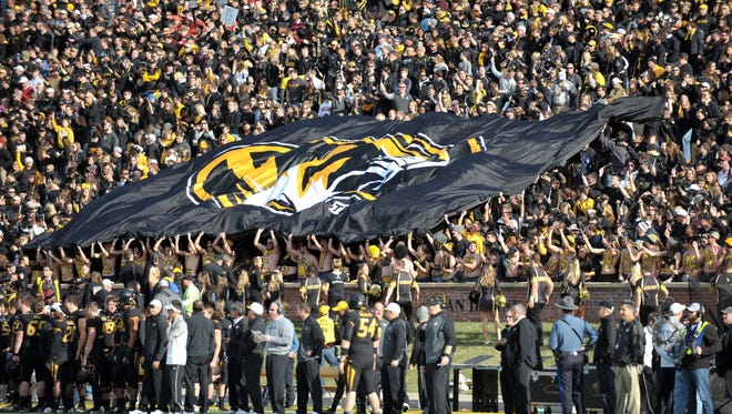 Missouri Tigers fans display a large flag before the game against the Arkansas Razorbacks at Faurot Field.
