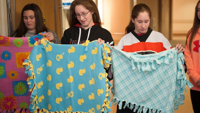 Rebecca (center) and Lindsay (right) Kligerman, 12-year-old twins from Marlton, donate 50 handmade blankets to the Virtua Voorhees NICU. The twins were born nearly 13 weeks too early. Weighing less than two pounds each, they were immediately placed on ventilators and were cared for in  Virtua's Neonatal Intensive Care Unit (NICU) for more than three months.