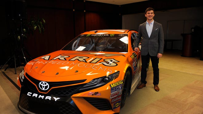 Daniel Suarez poses with his new car on Jan. 11 after being promoted to the NASCAR Cup Series by Joe Gibbs Racing.