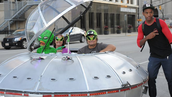 A fan poses with Steve Anderson's flying saucer car in Downtown Indianapolis.